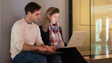 Image of a woman and man looking at a laptop together, the man is holding a closed laptop on his lap